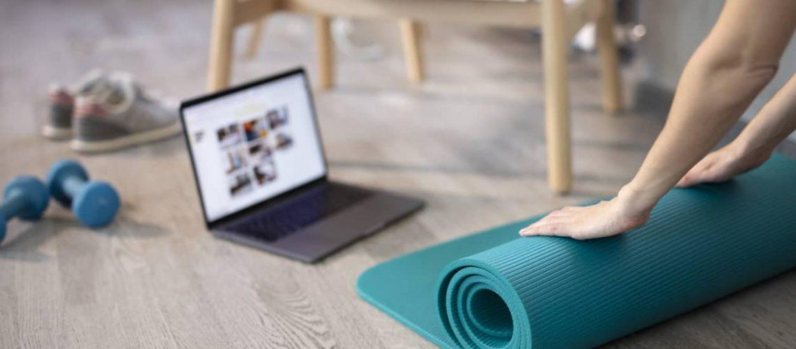 Preparing for training online. Mat, dumbbell, mat and laptop. Preparing for online fitness training at home with laptop and fitness mat. Online training, online fitness, stay home, quarantine, online training.