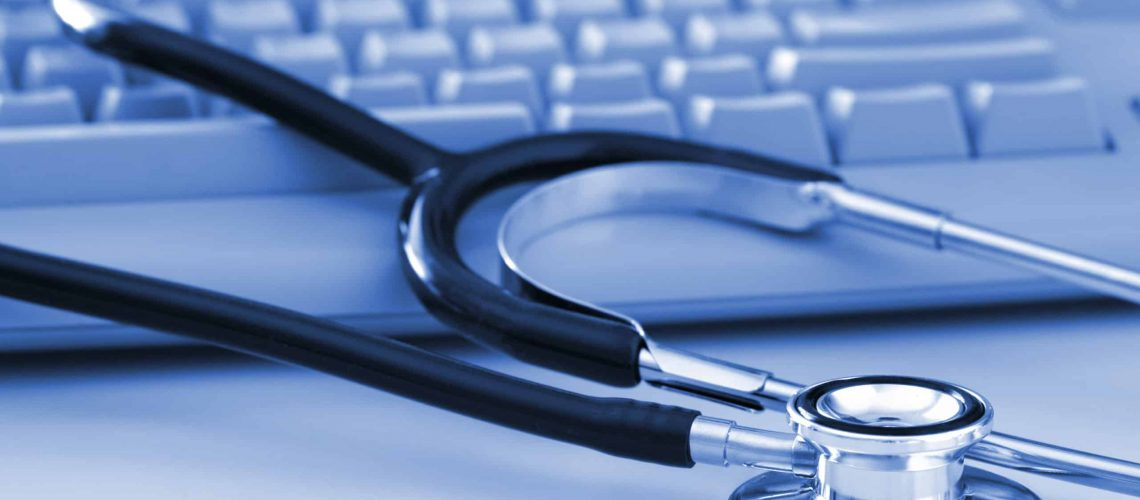 A stethoscope by a computer keyboard. Computer technology is an integral part of medicine, healthcare, and medical/health insurance today.