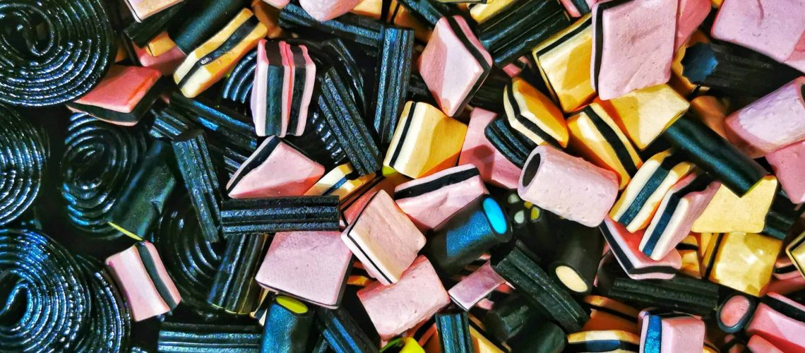 Unique view of a bin of black and mutli colored licorice candies.